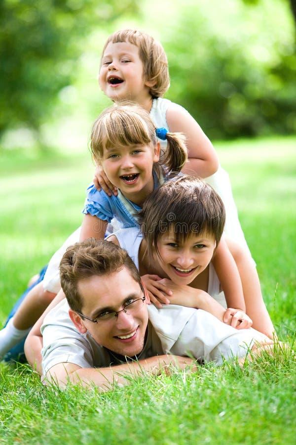 Familie, die auf Gras liegt lizenzfreies stockbild