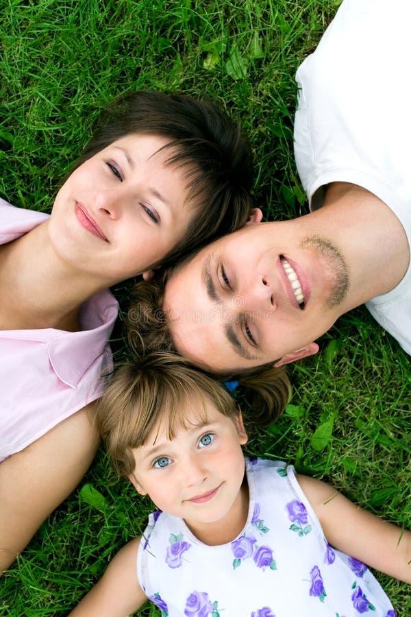 Familie, die auf Gras liegt stockbild
