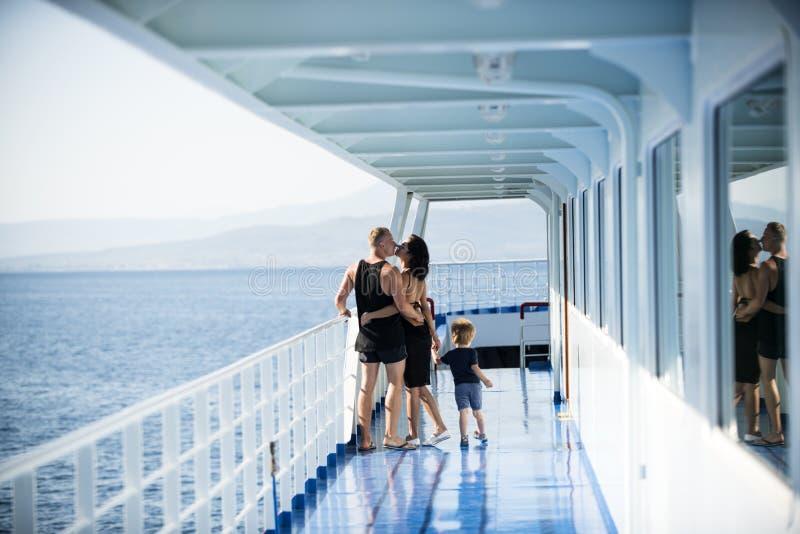 Familie, die auf Kreuzschiff auf sonniger Tagfamilie und Liebeskonzept reist Vater, Mutter und Kind stehen auf Plattform der Kreu lizenzfreie stockbilder