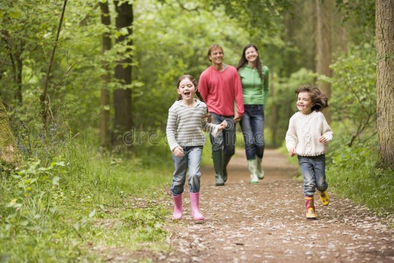 Familie, die auf Pfadholding-Handdem lächeln geht lizenzfreies stockfoto
