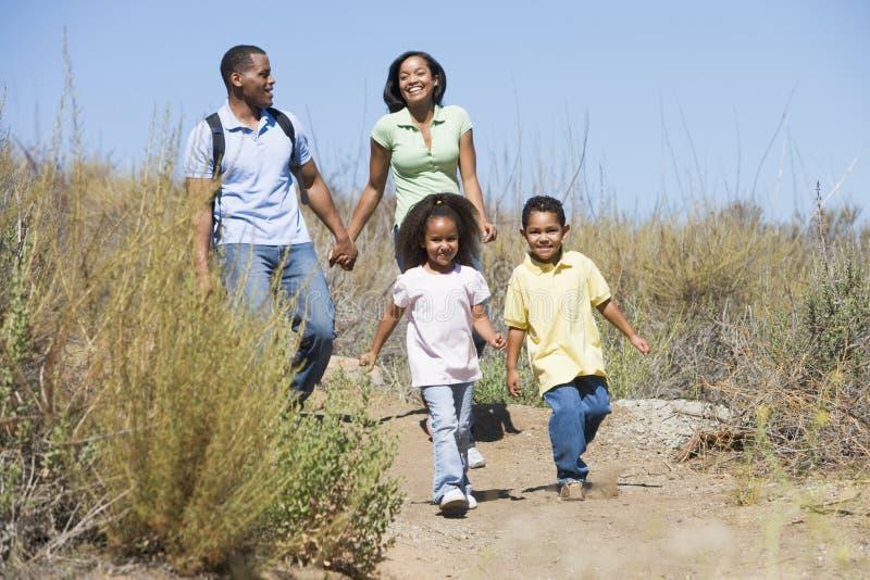 Familie, die auf Pfadholdinghände und -c$lächeln geht stockbilder
