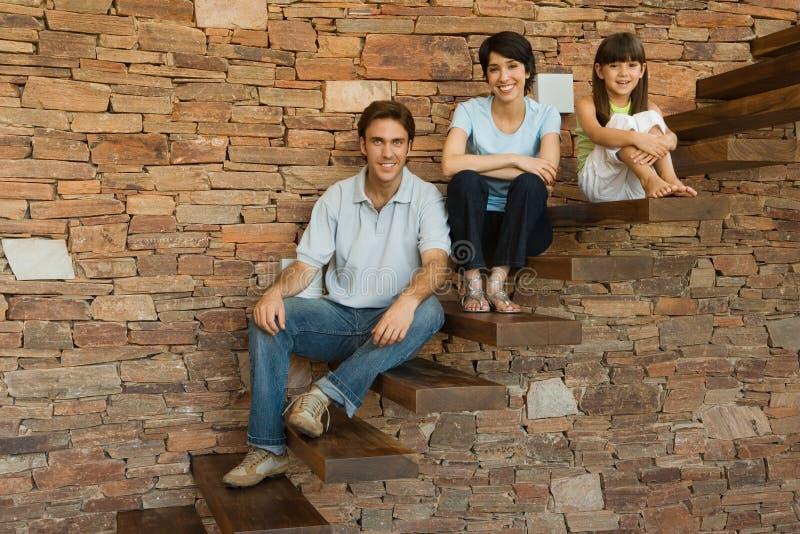 Familie, die auf Schritten sitzt lizenzfreie stockfotografie