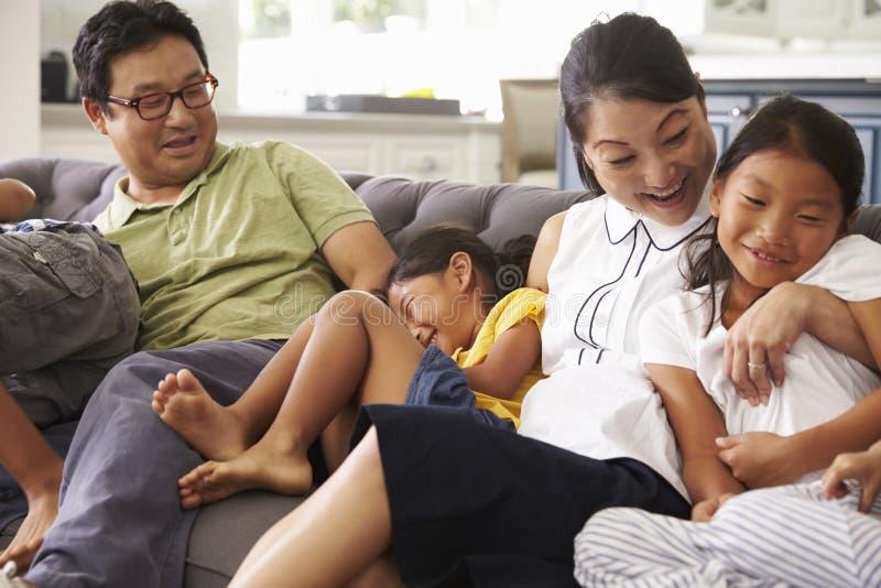 Familie, die auf Sofa At Home Together sich entspannt stockfoto