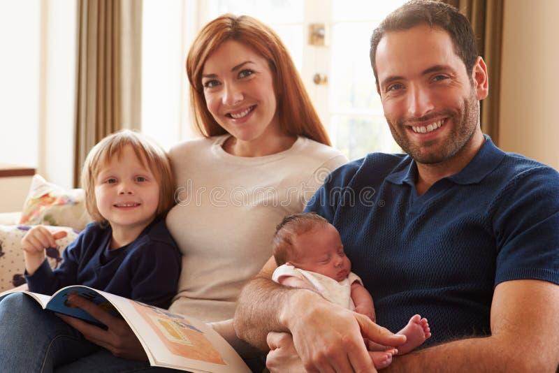 Familie, die auf Sofa With Newborn Baby sitzt stockfotografie