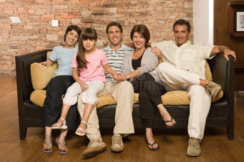 Familie, die auf Sofa sitzt lizenzfreie stockbilder