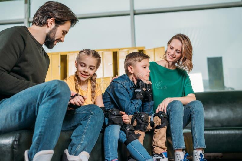 Familie, die auf Sofa vor dem Eislauf in Rollschuhe stillsteht lizenzfreie stockbilder