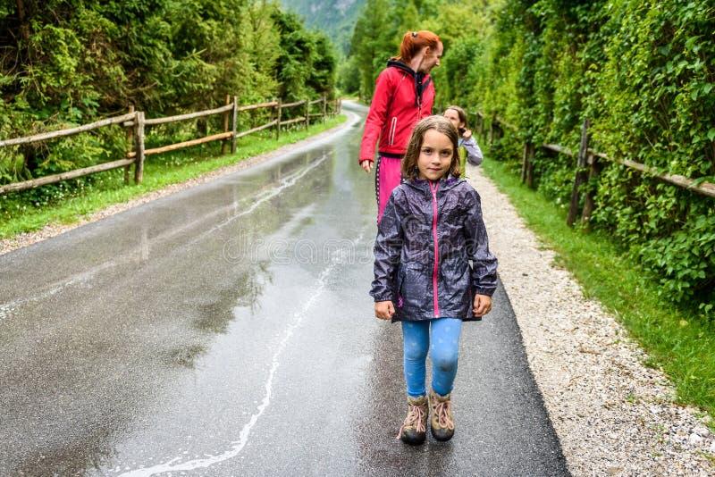 Familie, die auf Straße in der Natur an einem regnerischen Tag wandert lizenzfreies stockfoto
