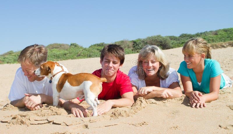 Familie, die auf Strand liegt lizenzfreie stockfotos