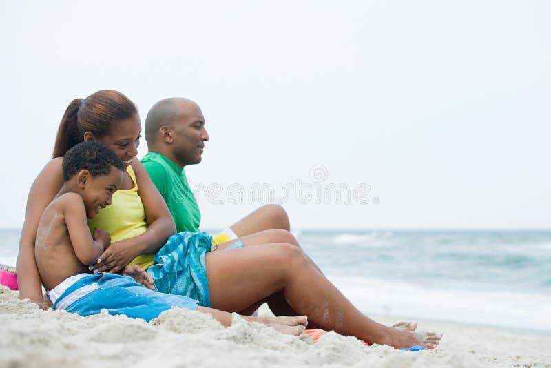 Familie, die auf Strand sitzt lizenzfreies stockfoto