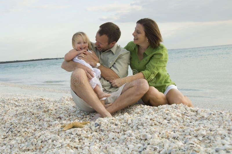Familie, die auf Strand spielt stockfotografie