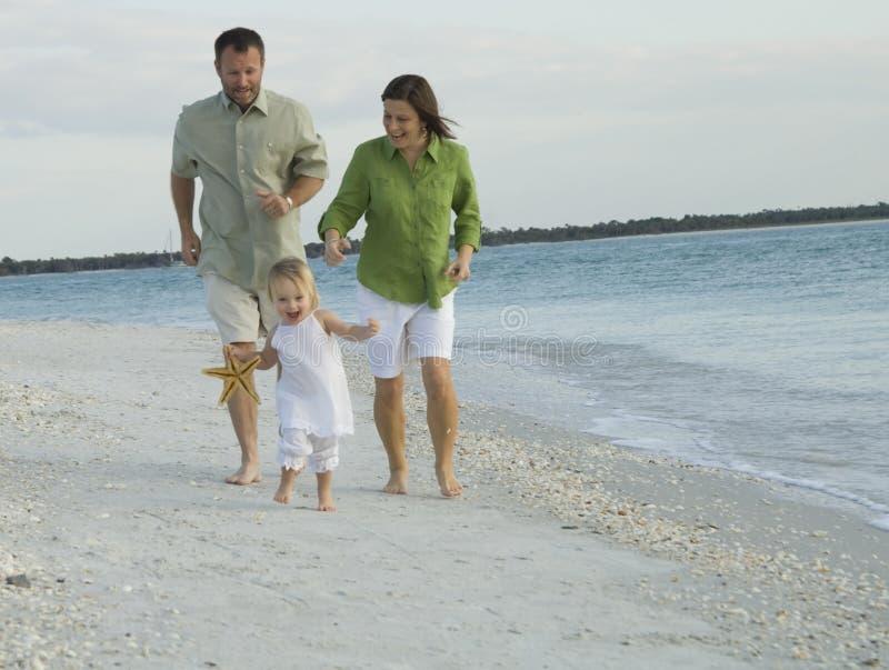 Familie, die auf Strand spielt stockfotos