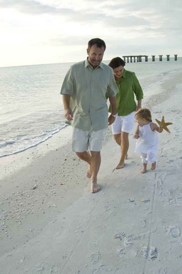 Familie, die auf Strand spielt lizenzfreie stockfotografie