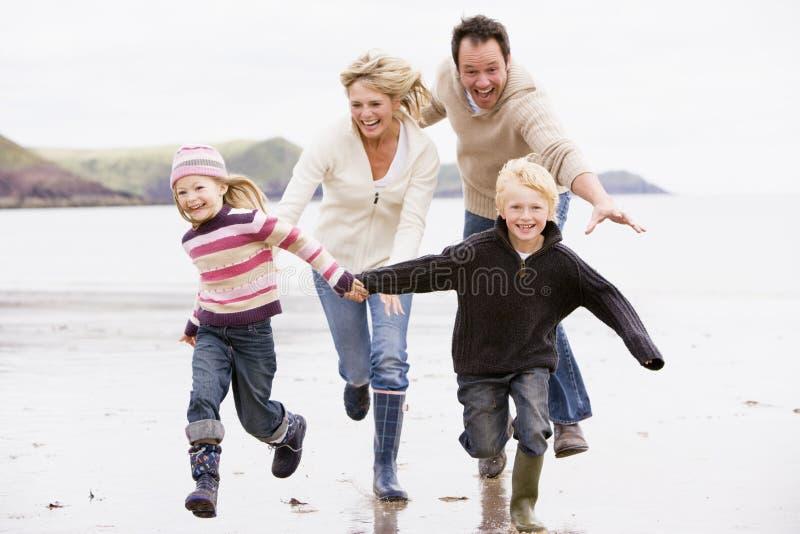 Familie, die auf Strandholdinghände läuft stockbilder