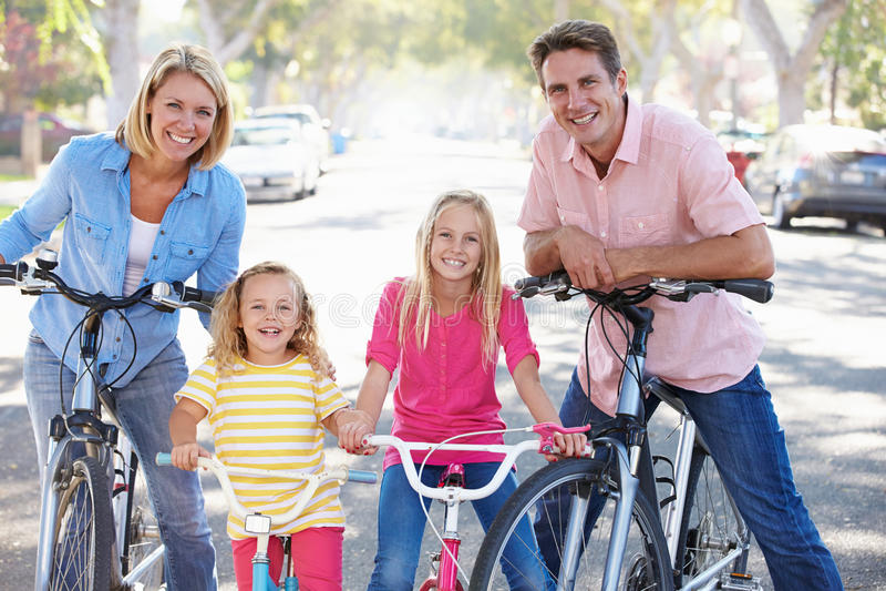 Familie, die auf Vorstadtstraße radfährt stockbilder