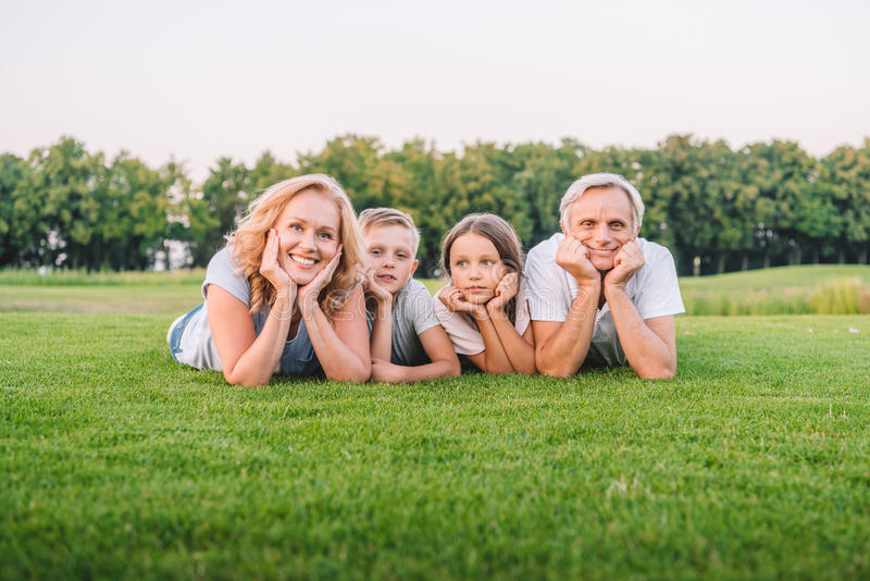 Familie, die auf Wiese liegt lizenzfreie stockfotografie