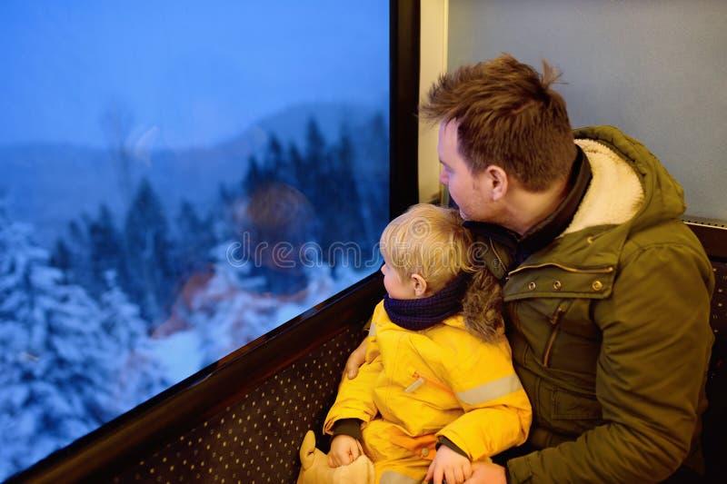 Familie, die aus dem Fenster des Zugs heraus während der Reise auf Zahnradeisenbahn/-Zahnradbahn in den Alpenbergen schaut stockbild