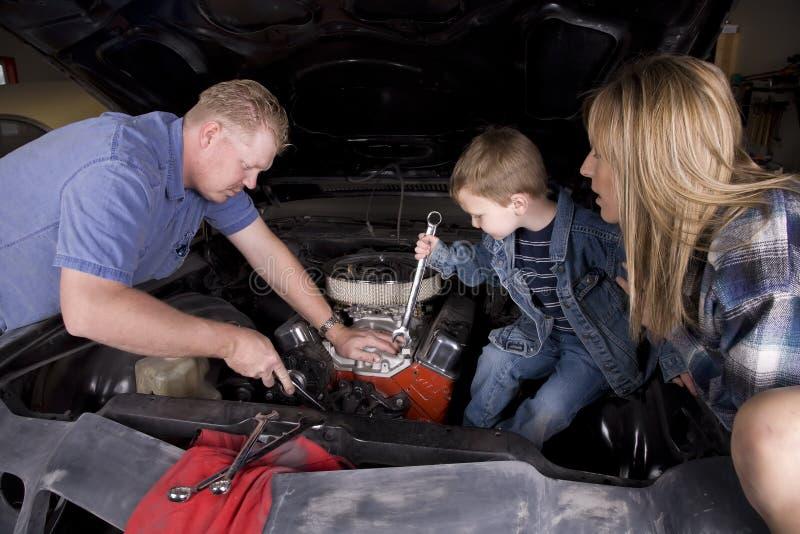 Familie, die an Auto arbeitet stockfoto