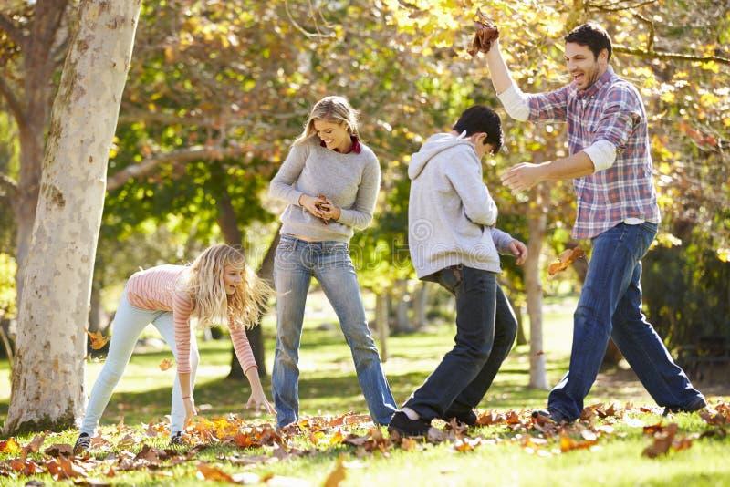 Familie die Autumn Leaves In The Air werpen stock afbeeldingen