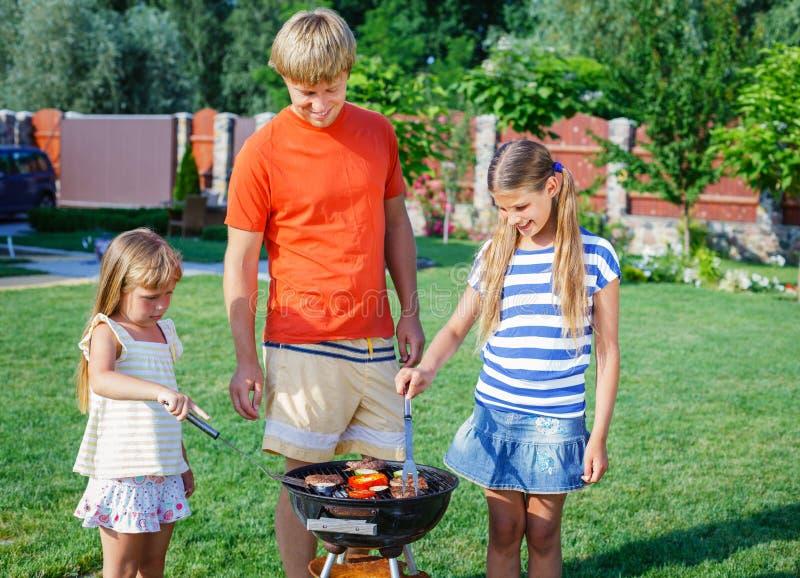 Familie die barbecue hebben royalty-vrije stock afbeelding