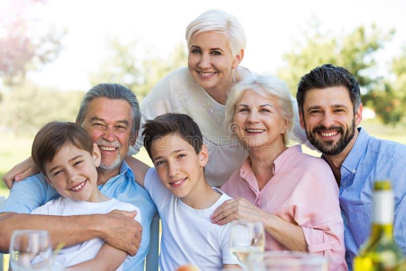 Familie, die bei Tisch draußen, lächelnd sitzt lizenzfreie stockfotos