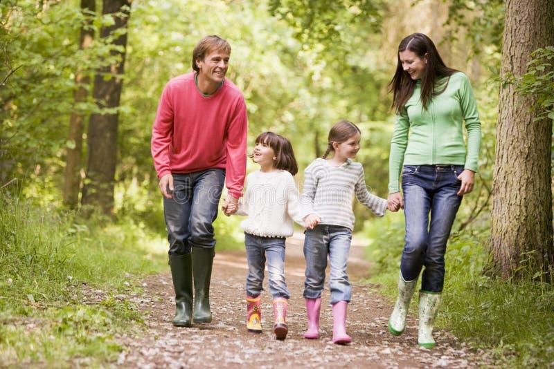 Familie die bij de handen van de wegholding het glimlachen loopt royalty-vrije stock afbeeldingen
