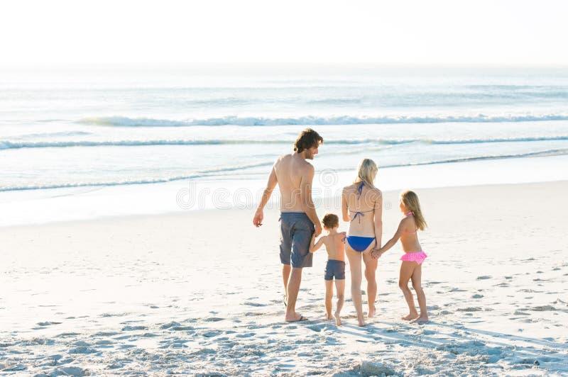 Familie die bij kust lopen stock fotografie