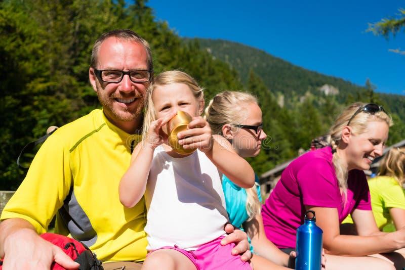 Familie, die Bruch vom Wandern in den Bergen hat lizenzfreie stockfotos