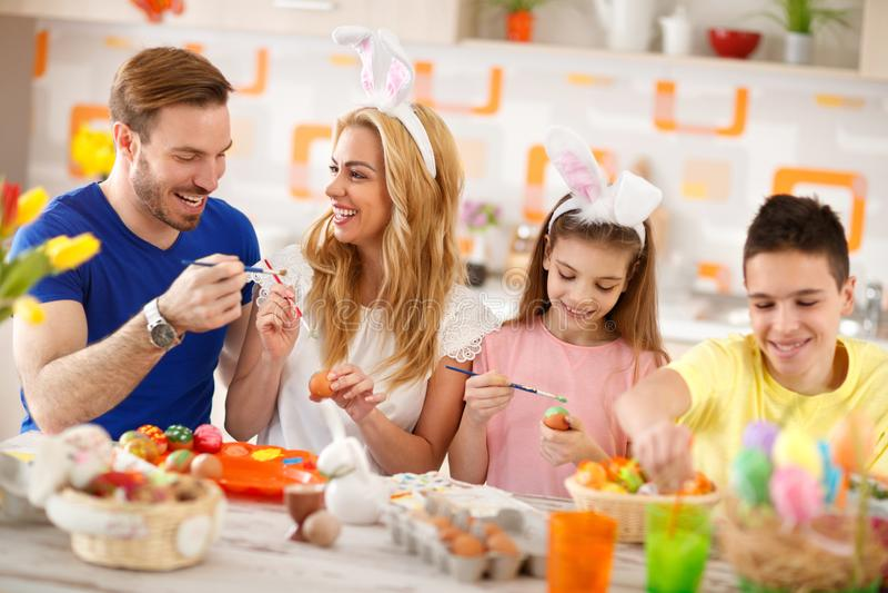 Familie, die bunte Eier Ostern färbt stockbilder