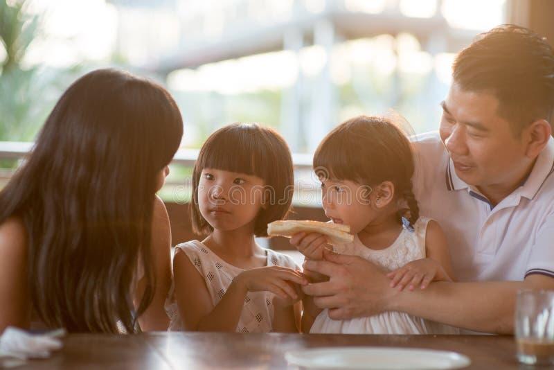 Familie, die am Café frühstückt stockbilder