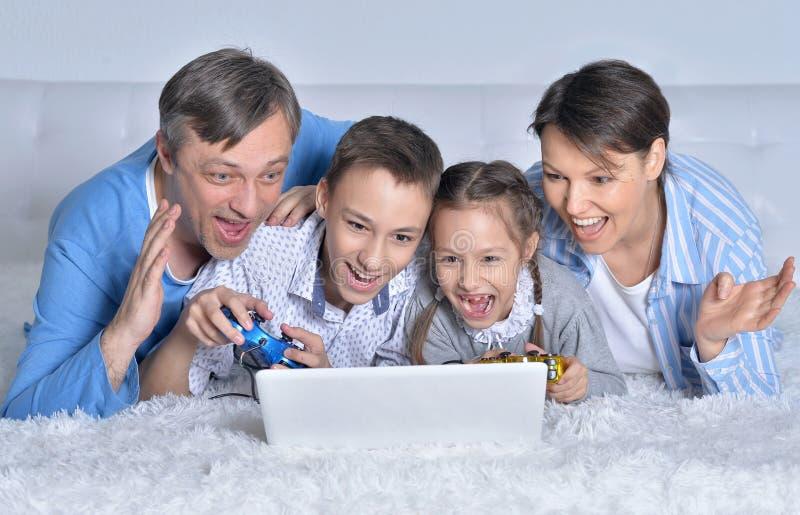 Familie, die Computerspiele spielt lizenzfreie stockbilder