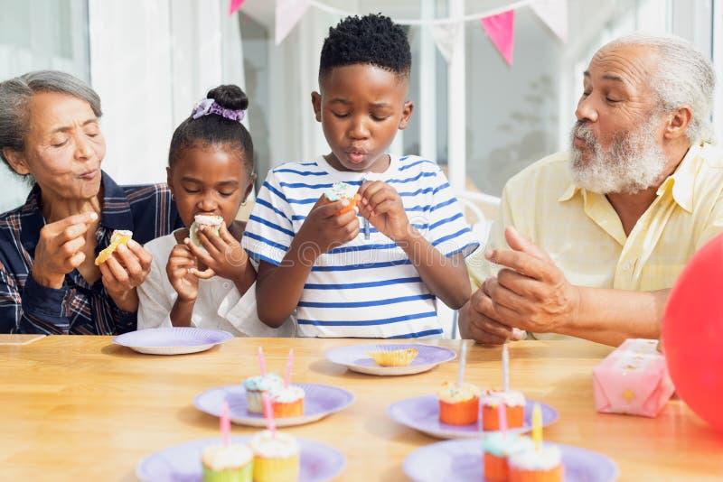 Familie die cupcakes eten royalty-vrije stock afbeeldingen