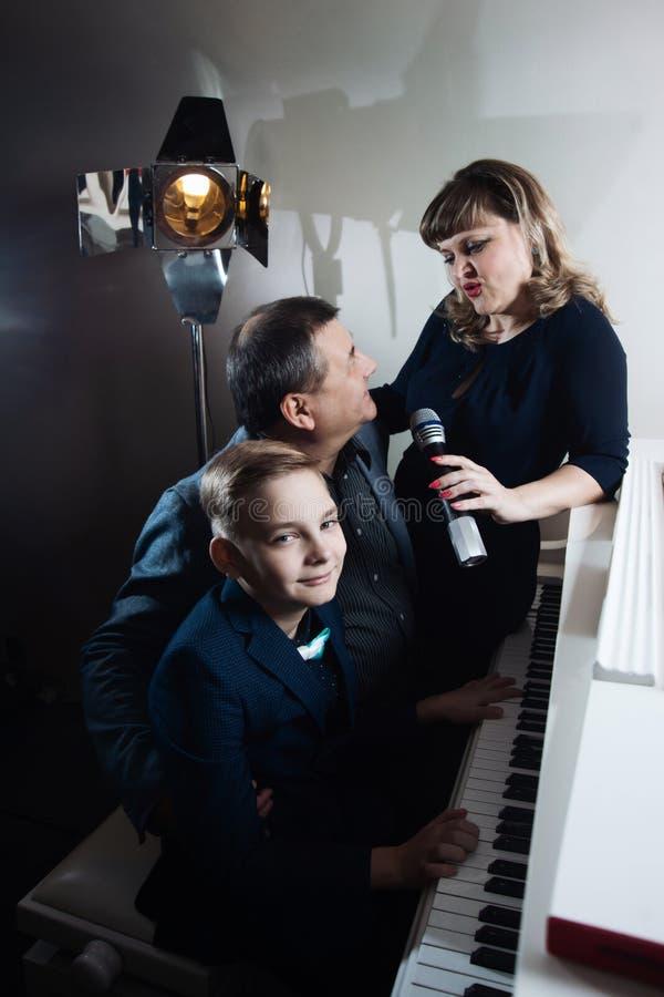 Familie, die das Klavier spielt und Lieder in das Mikrofon singt stockbild