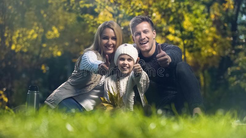 Familie, die Daumen oben auf Picknick im Herbstpark, Elternschaft lächelt und zeigt lizenzfreies stockbild