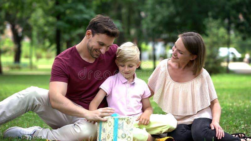 Familie die de doos van de zoonsgift, geven die jongen met goede tekens op school, zorg gelukwensen stock fotografie