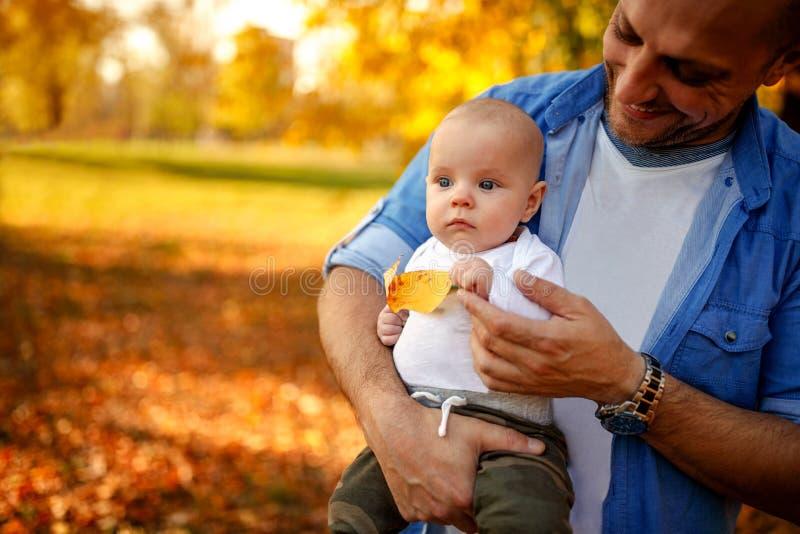 Familie die in de herfst park-vader genieten van met het kind stock afbeelding