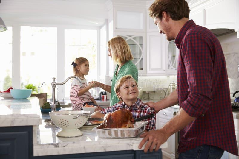 Familie die de Maaltijd van Braadstukturkije in Keuken samen voorbereiden stock foto