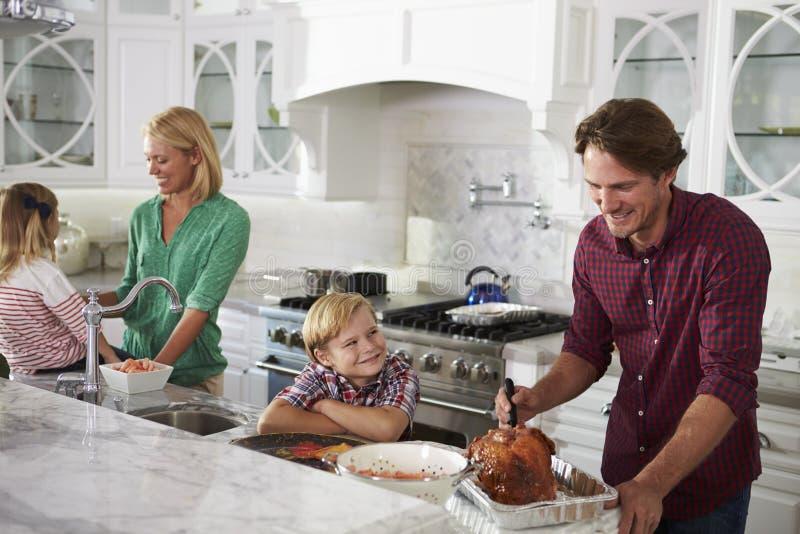 Familie die de Maaltijd van Braadstukturkije in Keuken samen voorbereiden royalty-vrije stock afbeelding