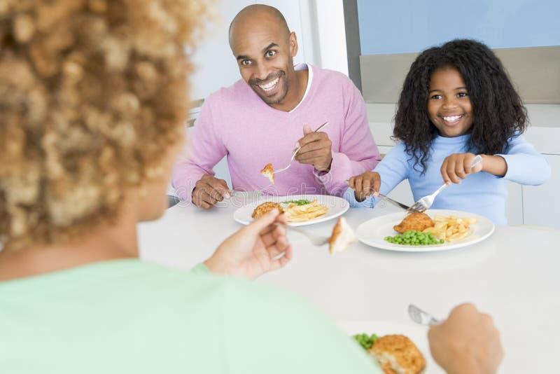 Familie die de maaltijd van A, etenstijd samen eet stock fotografie