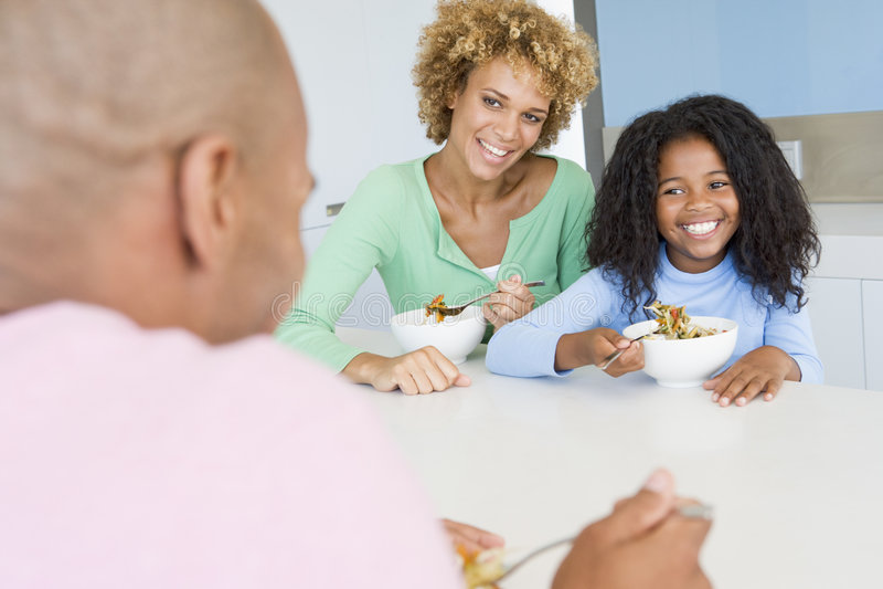Familie die de maaltijd van A, etenstijd samen eet stock foto's