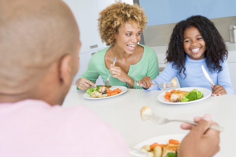Familie die de maaltijd van A, etenstijd samen eet stock foto