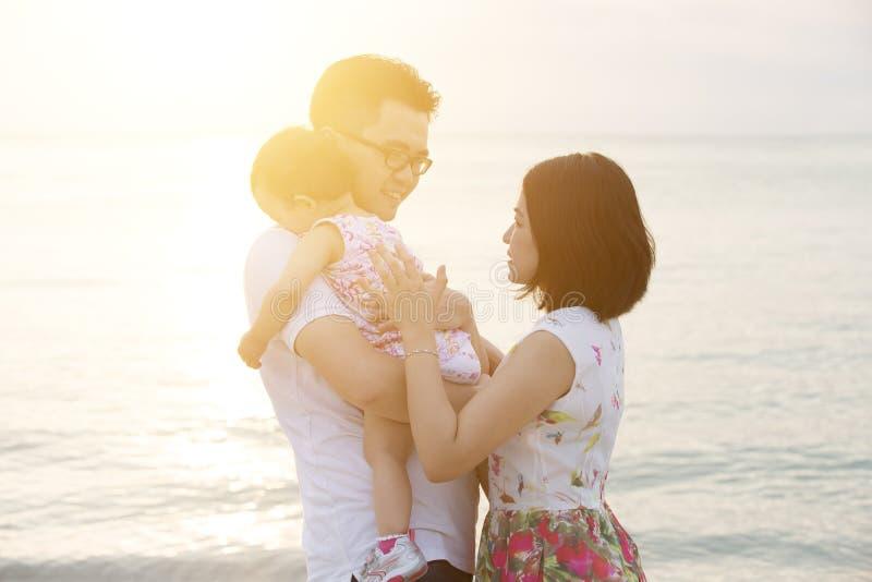 Familie die de zomer van vakantie genieten bij strand stock foto