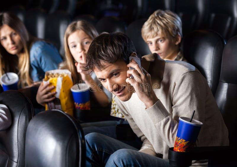 Familie, die den Mann verwendet Mobiltelefon im Theater betrachtet lizenzfreies stockfoto