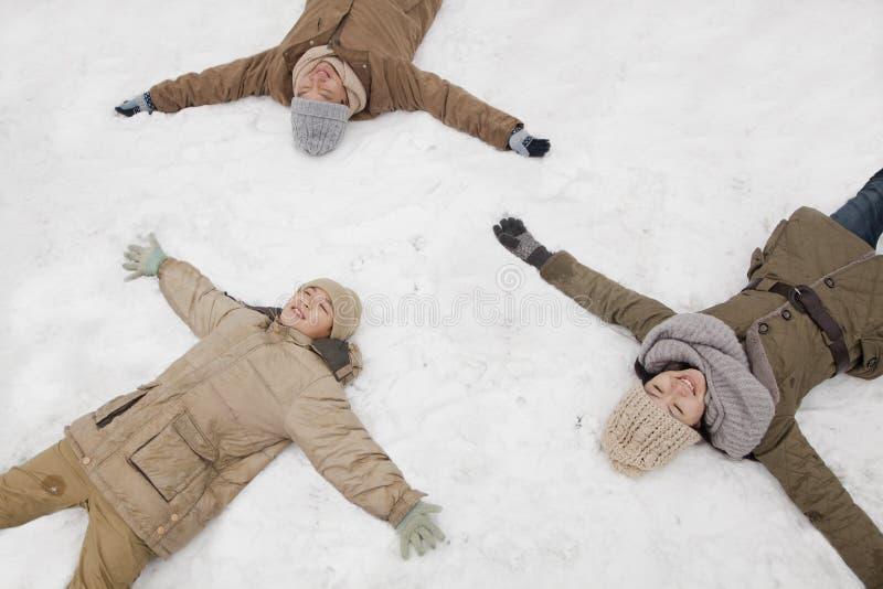 Familie, die in den Schnee macht Schneeengel legt lizenzfreie stockfotografie