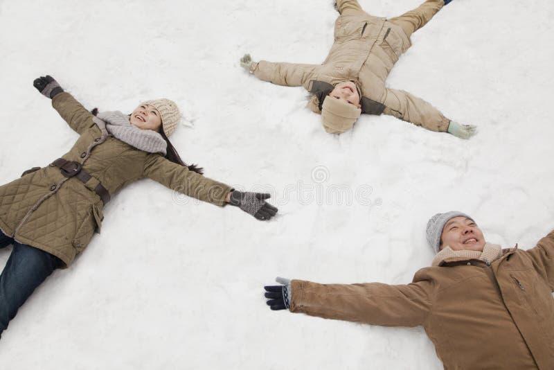 Familie, die in den Schnee macht Schneeengel legt stockbild