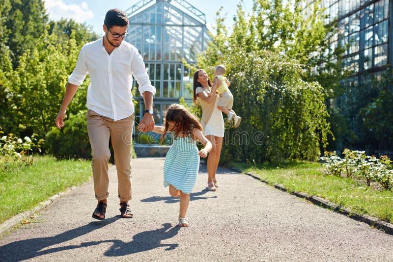Familie, die den Spaß im Freien hat Glückliche junge Eltern, Kinderspielen stockbild