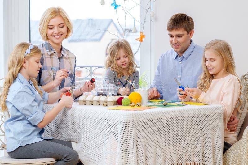 Familie, die den Spaß malt und verziert Ostereier hat lizenzfreies stockfoto