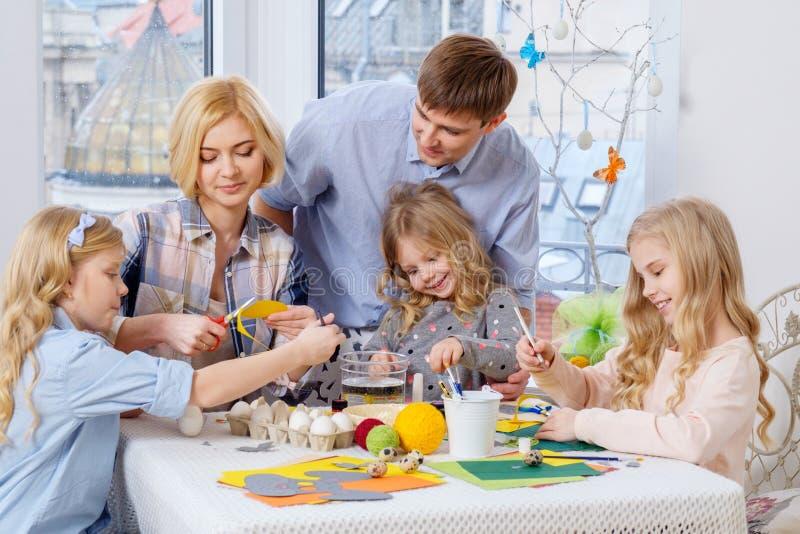 Familie, die den Spaß malt und verziert Ostereier hat lizenzfreie stockbilder