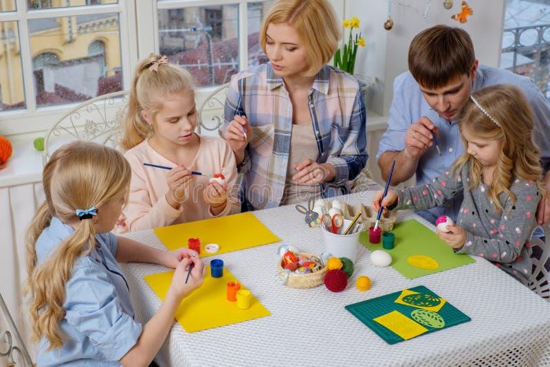 Familie, die den Spaß malt und verziert Ostereier hat lizenzfreie stockfotografie