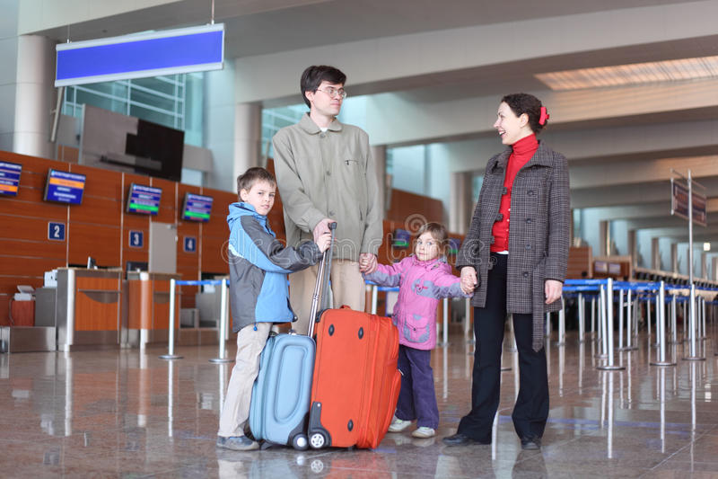Familie, die in der Flughafenhalle mit Koffern steht stockfoto