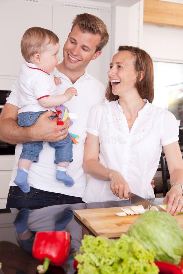 Familie, die in der Küche lacht lizenzfreies stockbild